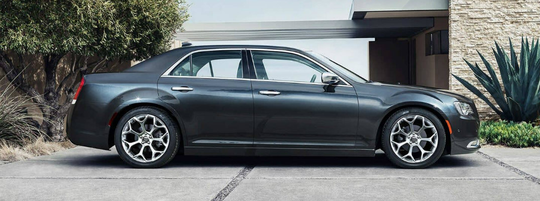 2019 Chrysler 300 exterior side shot with black gray paint color parked outside a luxury estate house