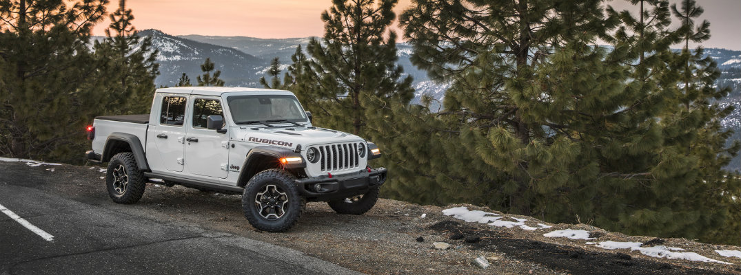 2020 Jeep Gladiator Rubicon pickup truck exterior shot with bright white paint color parked on the side of a country forest road