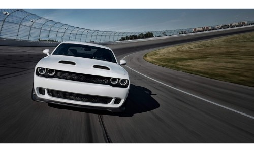 2019 Dodge Challenger exterior front shot of grille, headlights and fascia with white paint color driving around a racing track