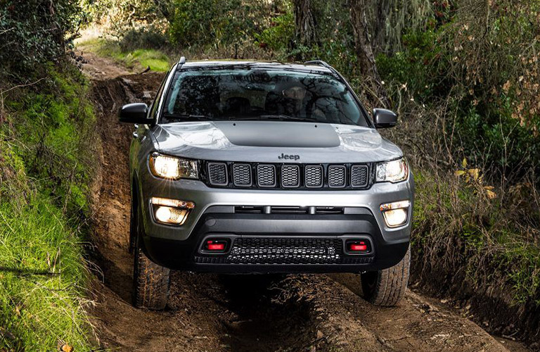 Front view of 2019 Jeep Compass driving through tree-lined road