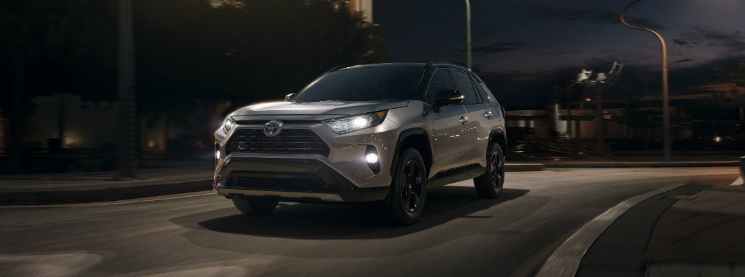 Silver 2019 Toyota RAV4 driving at night time on lit city street