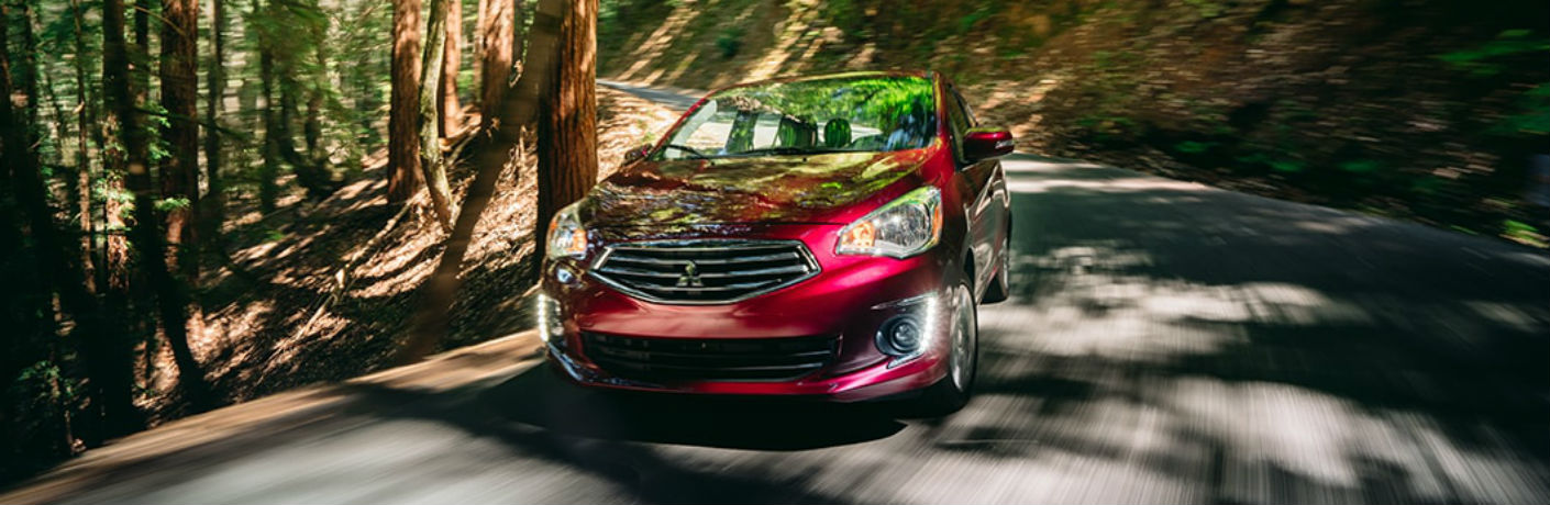 Exterior view of a red 2018 Mitsubishi Mirage G4 driving down a country road surrounded by trees