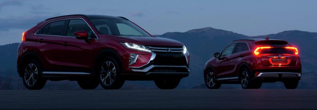 Two scarlet colored 2019 Mitsubishi Eclipse Cross SUVs idle in the desert dusk.
