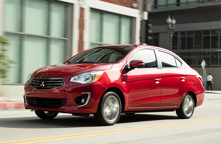 Red 2019 Mitsubishi Mirage G4 rolls happily down a city street in the sun.