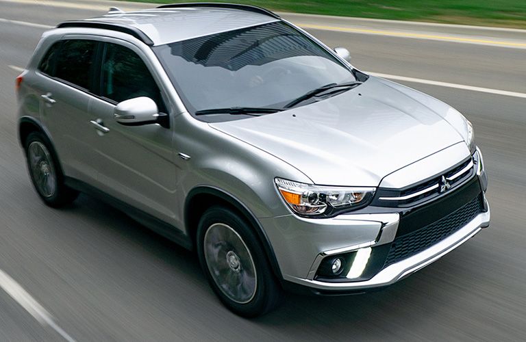Silver 2019 Mitsubishi Outlander Sport drives down a road.