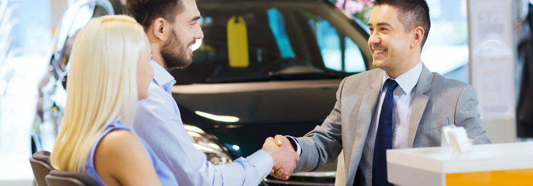 A salesman shakes the hand of a happy couple as he finalizes the sale of a car.