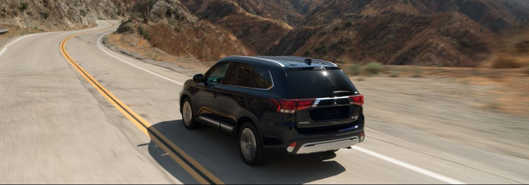 Black 2019 Mitsubishi Outlander drives along a curving desert highway for many miles.