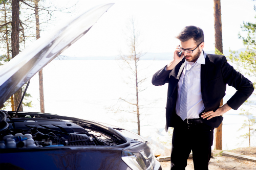 Man in suit calling for help with broken-down car