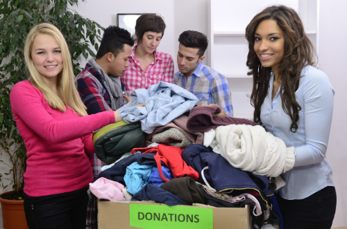 diverse group packing clothes into donation box