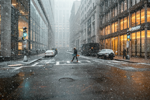 A lone individual crosses a crosswalk in a city as snow comes down and the pavement looks slick.