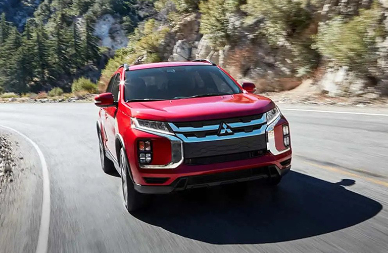 A red 2020 Mitsubishi Outlander Sport zooms around a highway curve in the sun.