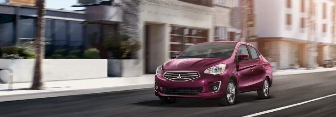 Fuschia 2020 Mitsubishi Mirage drives down a city street.