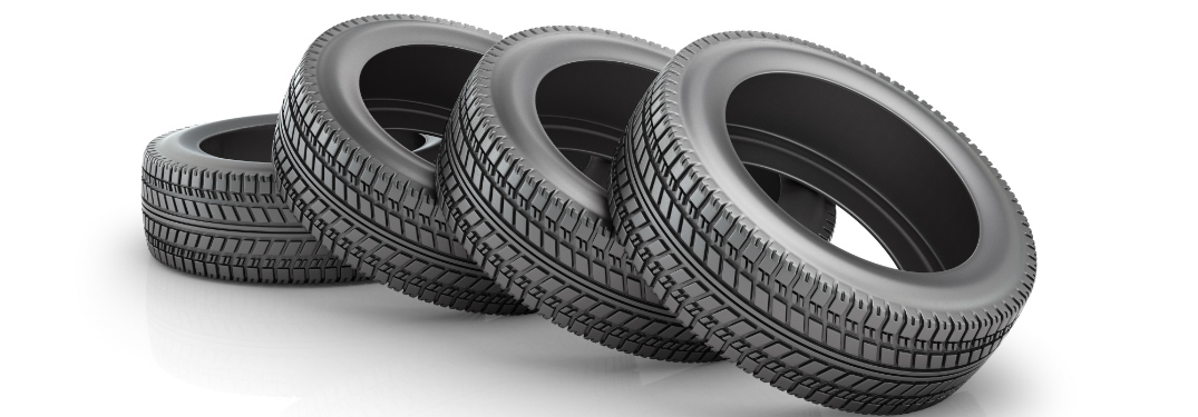 Four black tires lay in a toppled line on a white background.