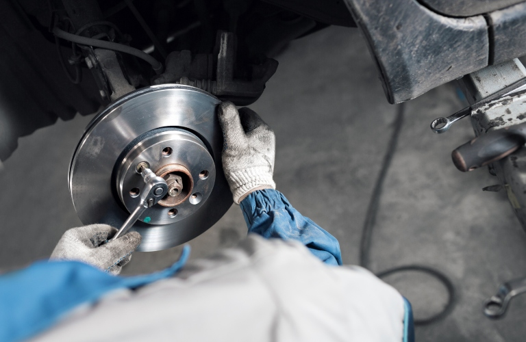 Mechanic unscrews a brake from a vehicle. First-person view.