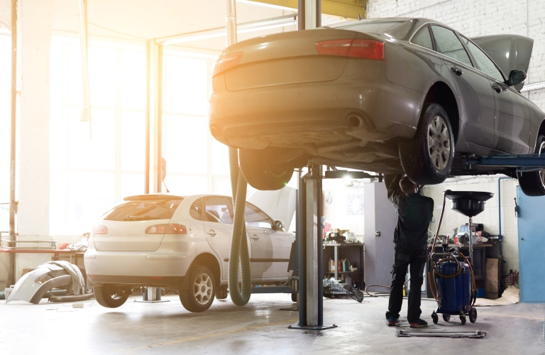 A car is on a lift in a maintenance shop. A mechanic works on it underneath as sunlight beams through the window.