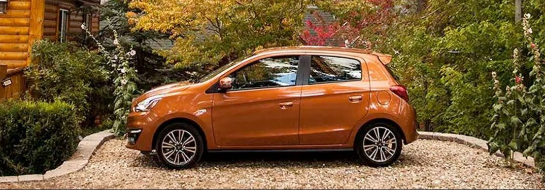 Orange 2020 Mitsubishi Mirage parked at a home in lovely nature.