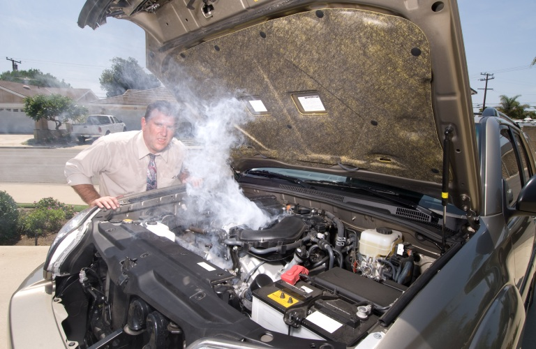 A man is a bit frustrated as he stands before a popped hood of his vehicle as it exhales a gust of steam.