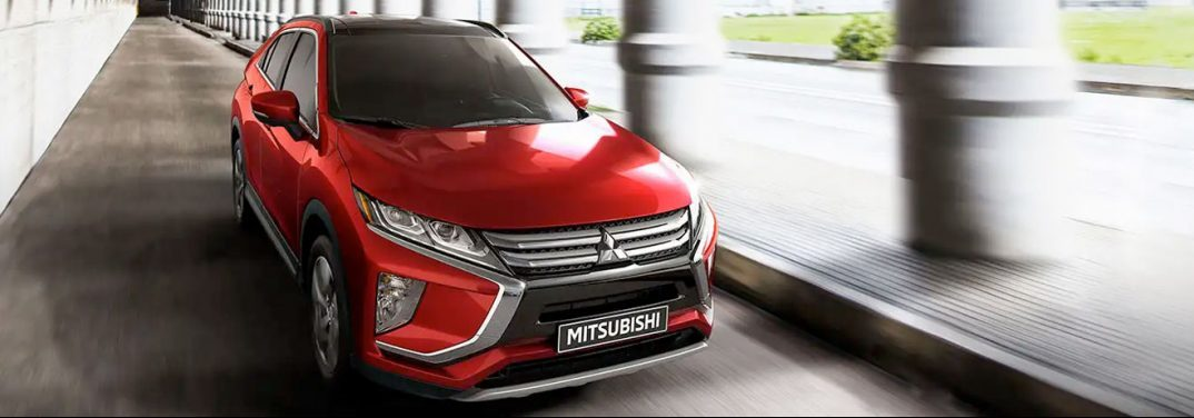 Red 2020 Mitsubishi Eclipse Cross driving through an ancient building.