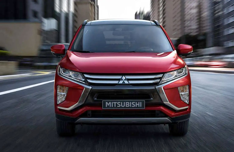 Head-on view of a red 2020 Mitsubishi Eclipse Cross driving up a city street.