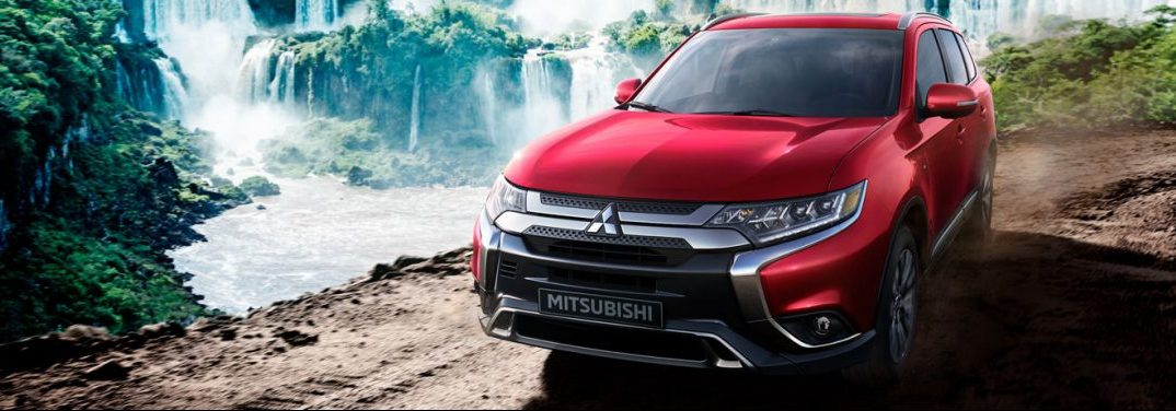 Red 2020 Mitsubishi Outlander parked by a series of waterfalls.