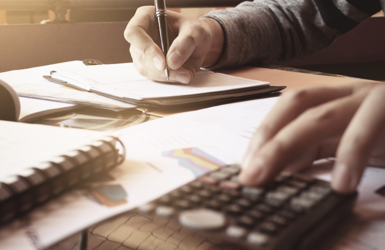 A man calculates finances intensely using a pen and a calculator.