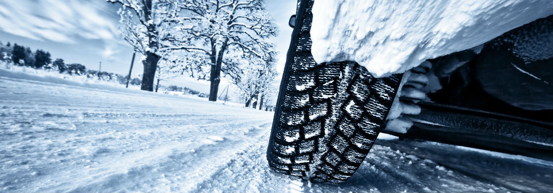 car tire driving on snowy road
