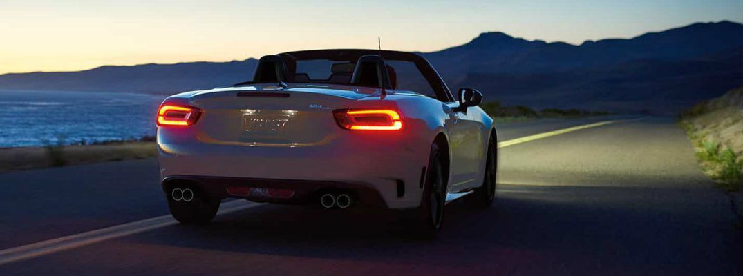 Rear view of 2018 Fiat 124 Spider driving at dusk
