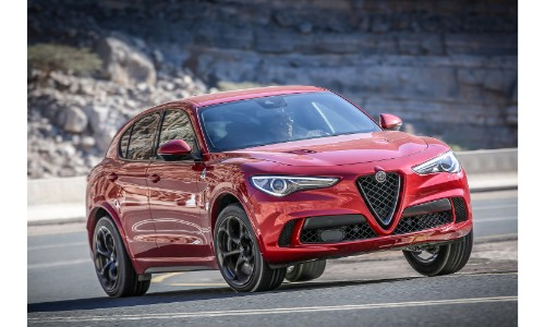 2019 Alfa Romeo Stelvio Quadrifoglio exterior shot with red paint color driving around a beach road with rocky cliffs behind it