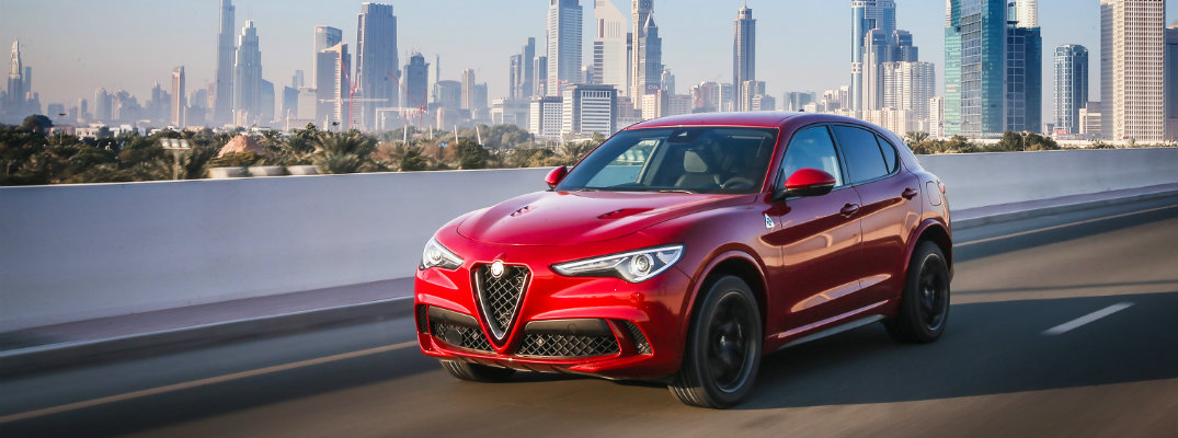 2019 Alfa Romeo Stelvio Quadrifoglio exterior shot with red paint color driving down a highway near water with a cityscape skyline background