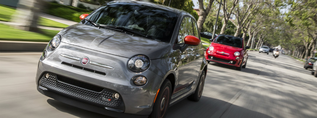 2019 Fiat 500e exterior closeup shot as it drives through a suburban neighborhood shadowed by trees