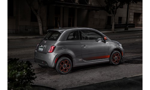 2019 Fiat 500e exterior shot with gray paint color parked on a patch of concrete in a dark city