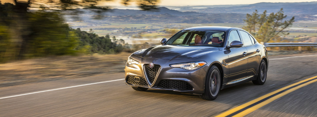 2019 Alfa Romeo Giulia exterior shot with gray paint color driving on a lush mountain highway road with green hills as a sunset sky behind it
