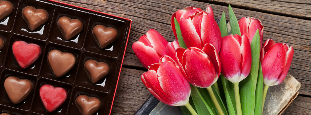 a bouqet of red tulips next to a box of heart shaped chocolates
