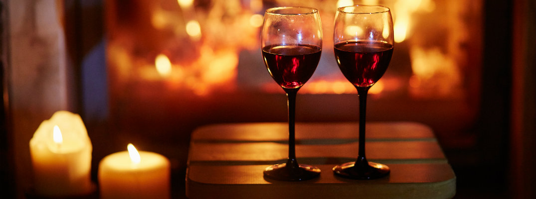 a couple of glasses of red wine set on a stool near lit candles and a fireplace for a romantic Valentine's Day dinner