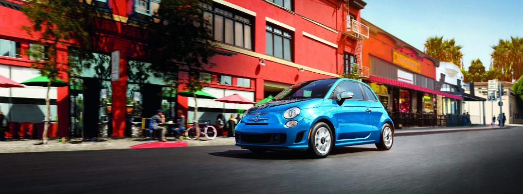 2019 Fiat 500 exterior wide shot with blue paint color driving by a set of brick apartment buildings