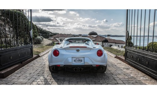 2019 Alfa Romeo 4C Spider exterior rear shot with white paint color park on a brick path at the gates of a villa