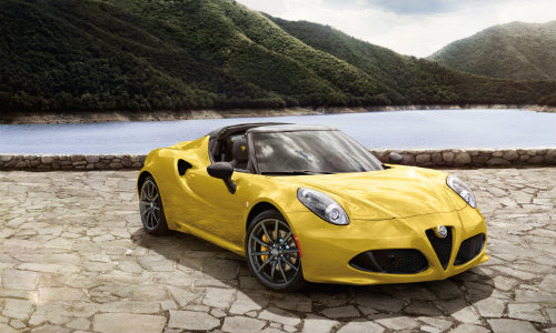 2019 Alfa Romeo 4C Spider exterior shot with yellow paint color parked on dry and cracked earth near a lake and grassy mountains