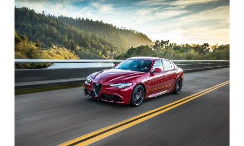 2019 Alfa Romeo Giulia Quadrifoglio exterior shot with red paint color driving down a highway with green forest trees in the background