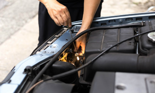 a service technician fixing a problem with a car's headlights under the hood