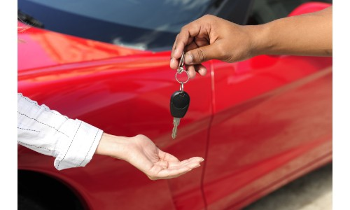 man handing over keys to a woman in front of a red car