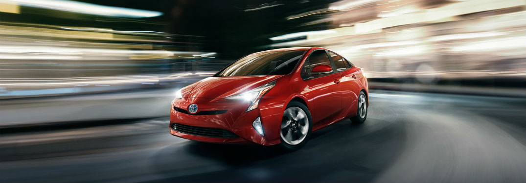 Driver side exterior view of a red 2018 Toyota Prius