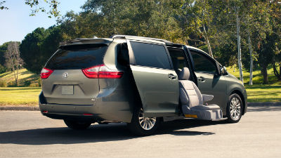 2018 Toyota Sienna exterior back fascia and passenger side with door open and seat lowered