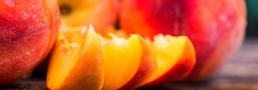 close up of three slices of peaches with whole peaches in background