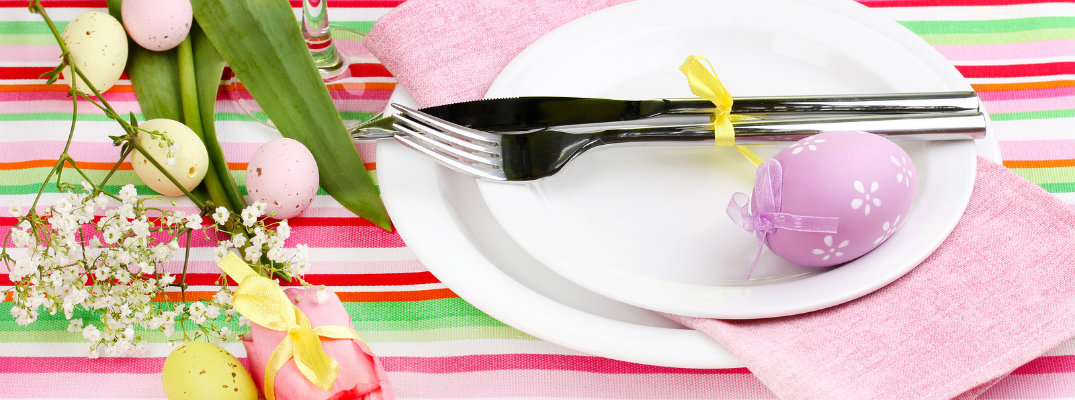 Easter dinner table setting with bright colors, fork and knife, and eggs
