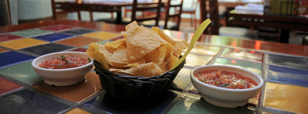 tortilla chips and salsa on a table in a mexican restaurant for cinco de mayo celebrations