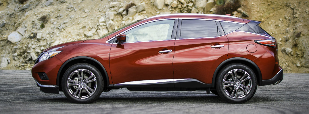 2018 Nissan Murano exterior side shot cayenne red parked next to a rocky mountain hill background