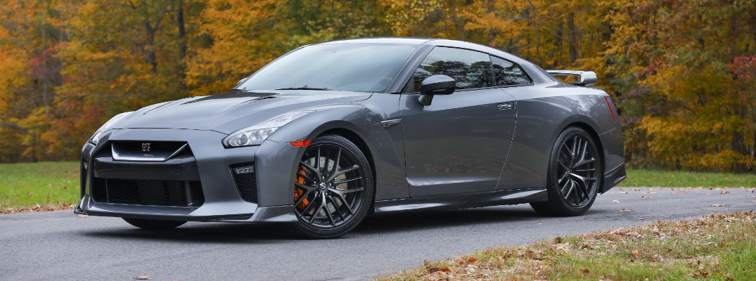 2018 Nissan GT-R roadster exterior super silver color parked on a curving road next to fall trees and leaves