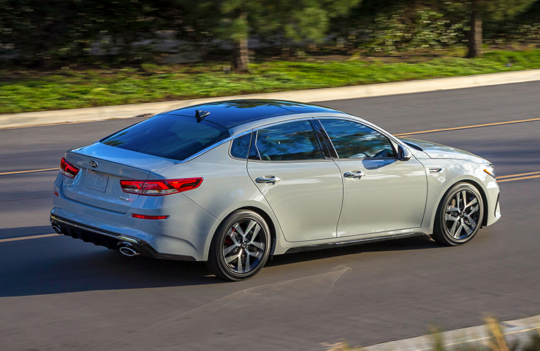 Low-riding 2019 Kia Optima driving on empty rural road