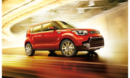 2018 Kia Soul exterior shot red paint job driving through a blurry, lit tunnel