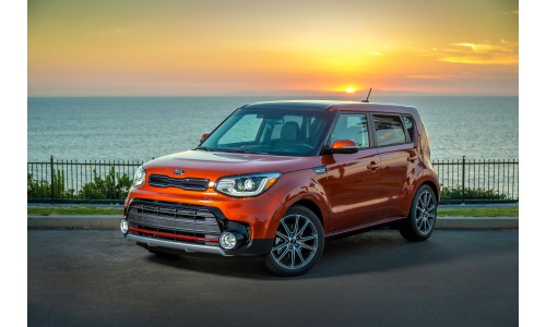 2019 Kia Soul exterior shot orange paint job parked by a waterfront with a fence, sea, and setting sun